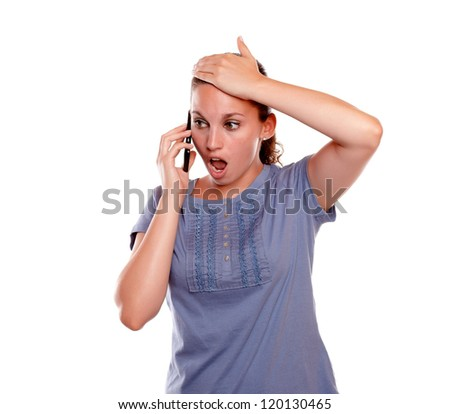 Surprised young female speaking on mobile phone on blue shirt standing over white background - stock photo