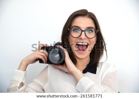Surprised young funny woman holding camera - stock photo