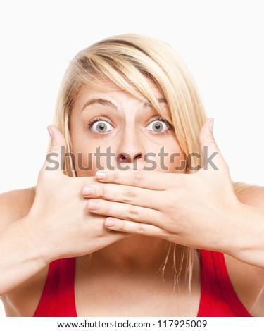 surprised young girl covering mouth with her hands looking