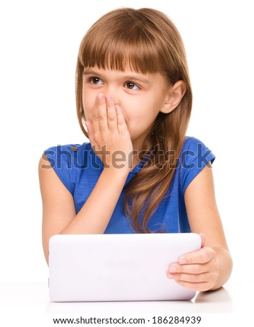 Surprised young girl is using tablet while studying, isolated over white - stock photo