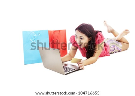 Surprised young girl with a laptop and a credit card isolated on white