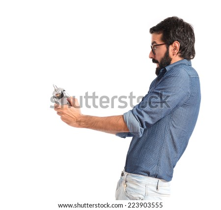Surprised young hipster man holding a clock - stock photo