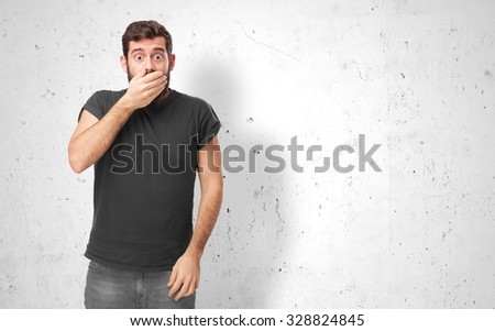 surprised young man covering mouth - stock photo