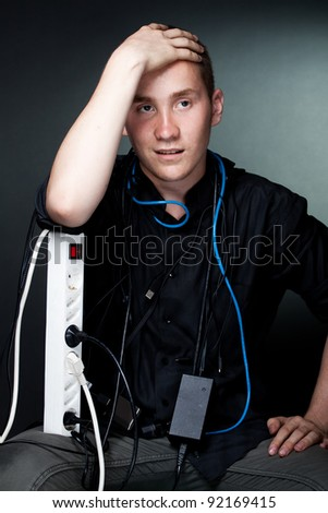 Surprised young man entangled in the wires, clutching his head