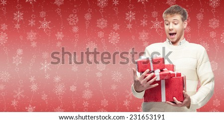 surprised young man holding cristmas gift over winter snowflakes background - stock photo