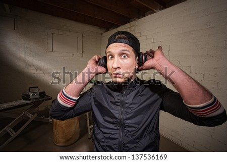 Surprised young man holding earphones over ears - stock photo