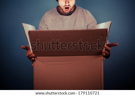 Surprised young man is opening a large cardboard box with something exciting inside it - stock photo