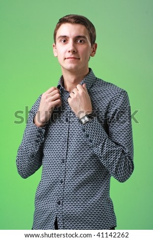 surprised young man standing against green background