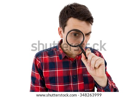 Surprised Young man student holding magnifying glass looking to something isolated over white background.