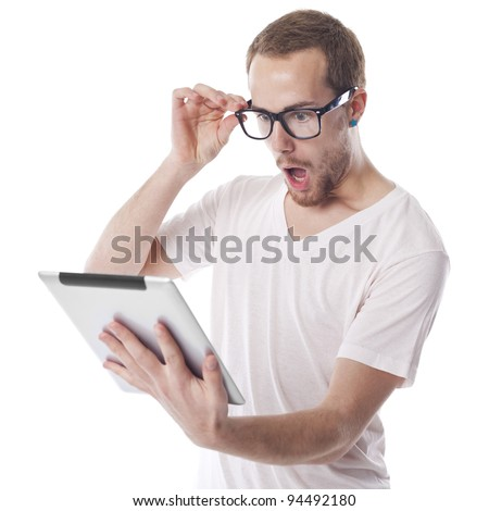 Surprised Young Nerd Smart Guy Looking At Tablet Computer - stock photo