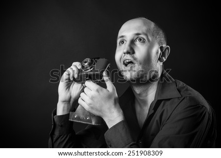 surprised young photographer with retro camera - stock photo