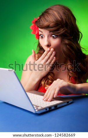 Surprised young woman at a computer - stock photo