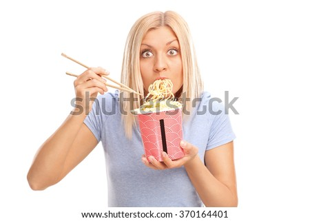 Surprised young woman eating Chinese noodles and looking at the camera isolated on white background - stock photo