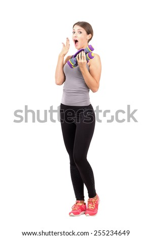 Surprised young woman holding aerobic foam dumb-bells. Full body length portrait isolated over white background. - stock photo