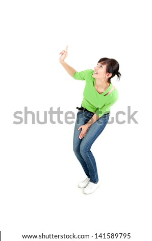 surprised young woman in green blouse pointing up, full length, white background - stock photo