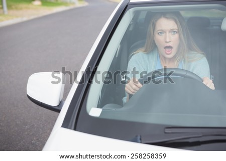 Surprised young woman in her car - stock photo