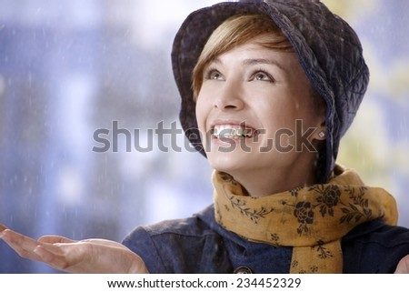 Surprised young woman in rain, smiling and looking up. - stock photo