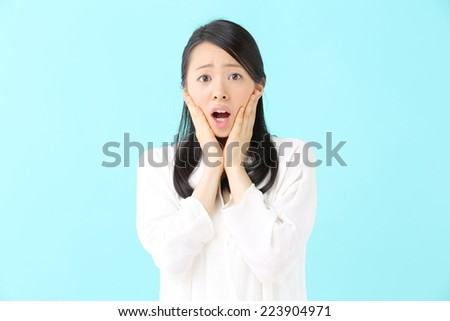 surprised young woman isolated on blue background - stock photo