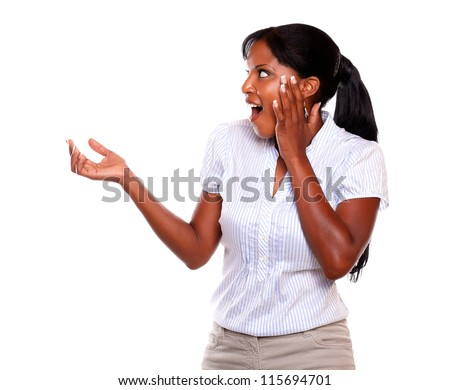 Surprised young woman looking to her right hand against white background - stock photo