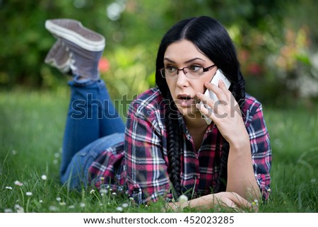 Surprised young woman lying on her stomach on the grass and talking on cell phone. Teenager lifestyle concept - stock photo
