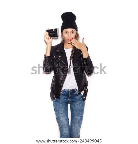 Surprised young woman making photo using noname retro camera. White background, not isolated - stock photo