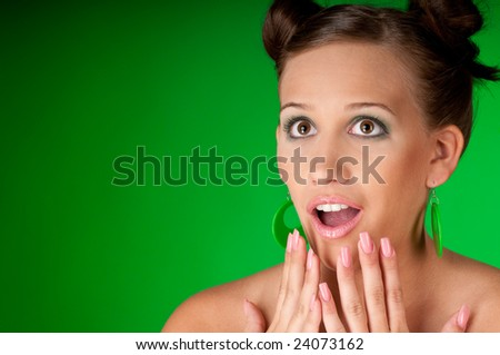 Surprised young woman on green background