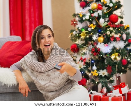 Surprised young woman watching TV near Christmas tree - stock photo