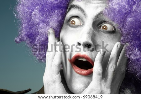 Surprising clown with purple wig on a blue background
