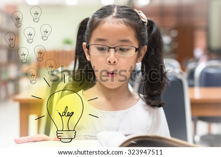 Surprising creative idea lighttbulb pop up from book in front of little asian child girl with eyeglasses (Selective focus): Student kid reading book in library looking at light bulb with excitement - stock photo