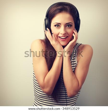 Surprising happy woman in headphones listening the music. Vintage portrait - stock photo
