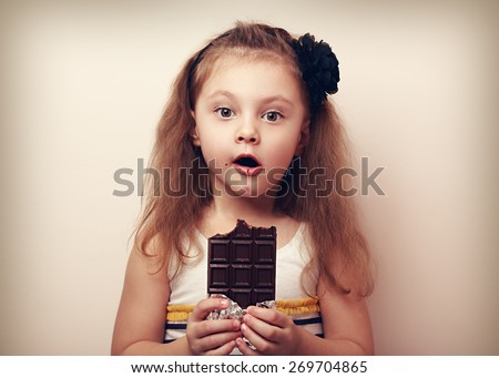 Surprising kid girl looking with big eyes and holding chocolate. Vintage portrait