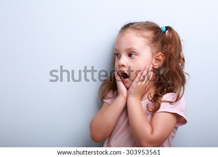 Surprising kid girl with opened mouth and hand near face looking on blue copy space background - stock photo
