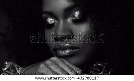 Surreal black and white close-up portrait of young african american female model with gold glossy makeup. Face art. Fashion concept - stock photo