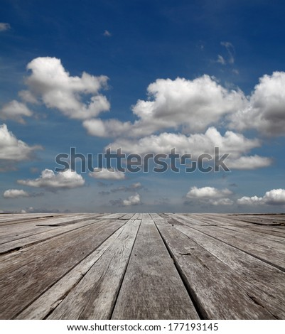 Surreal blue cloudy sky in the horizon of an empty grungy timber deck platform.  - stock photo