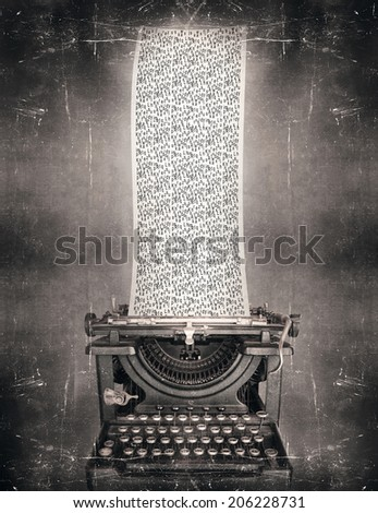 Surreal imagine in black and white of a beautiful classic old fashioned typewriter with a very long paper full of the alphabet letters in a vintage style - stock photo