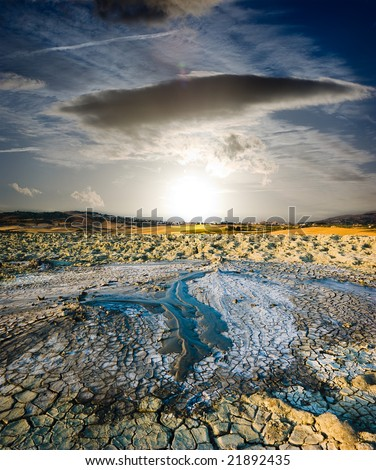 surreal landscape volcano erupted liquid mud to sunset - stock photo