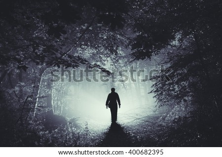 surreal light in dark forest and man silhouette - stock photo