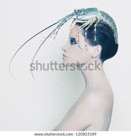 Surreal portrait of young lady with lobster on her head - stock photo