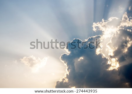 Surreal sun rays are striking through the clouds - stock photo