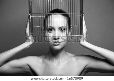 Surrealistic portrait of young woman with cage. Black and white photo