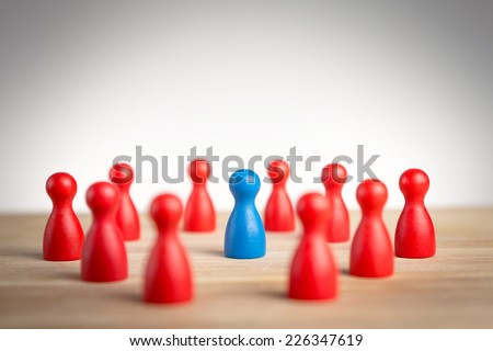 Surrounded by adversity or praised for being different concept with figurines - stock photo