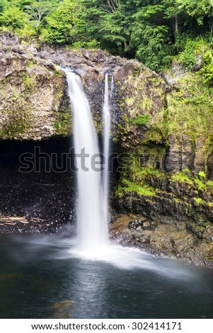 Surrounded by lush vegetation, a small waterfall in Hilo Hawaii forms cascading flows into a natural pool.R - stock photo