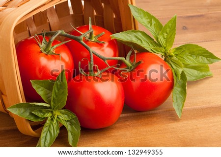 Surrounded by sweet basil, four red juicy vine ripened tomatoes fall out of a woven basket. A wooden cutting board provides the final resting place for the tomatoes before they are sliced open. - stock photo