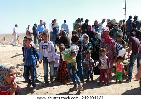 SURUC, TURKEY-SEPTEMBER 20, 2014: Turkey opened its border to Syrians fleeing the town of Kobane in fear of an Islamic State attack. Tens of thousands have fled to Turkey on september 20, 2014.  - stock photo