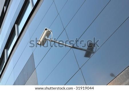 Surveillance camara on glass facade - stock photo
