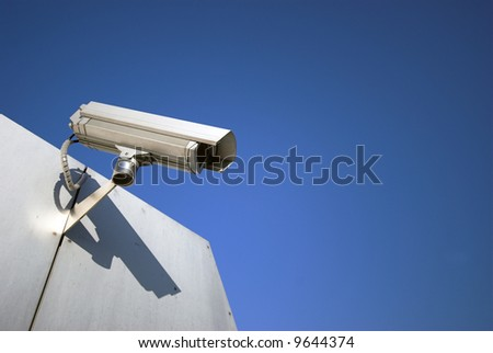Surveillance camera on building – sun and sky blue