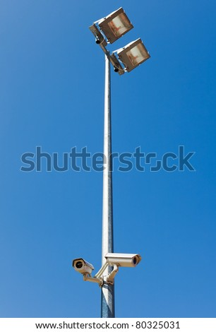 Surveillance camera on light pole in parking