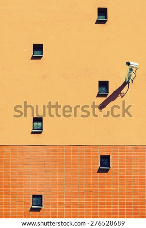 Surveillance camera on orange wall with small windows, filter applied for graphic effect - stock photo