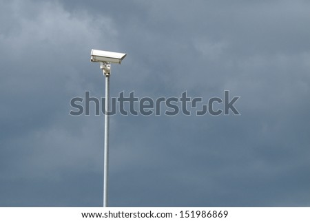 Surveillance camera on stormy sky background - stock photo