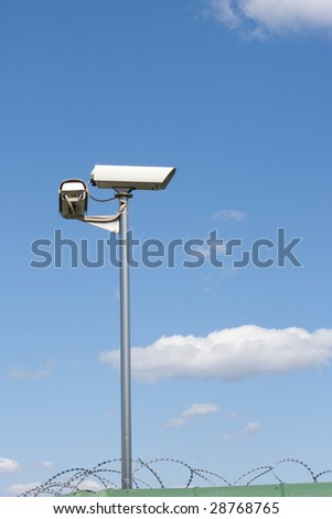 Surveillance camera on the wall with barbed wire on blue sky background